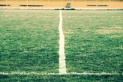 Cross of painted white lines on natural football grass. Artificial green turf texture. Royalty Free Stock Photo