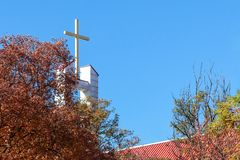 Cross peaking above the red roof of Catholic church on the blue sky background; autumn trees on the front view. royalty free stock photos