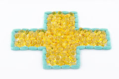 Cross of pills and capsules. Golden yellow capsules inside an outline of blue pills that are formed in a cross shape in a white background royalty free stock photo