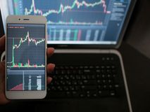 Cross-platform services for trading on the exchange. Hand with the phone on the background of a laptop royalty free stock images