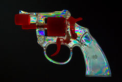 Cross polarized image of a toy gun. Cross polarized image of a toy Colt Detective Special gun shows rainbow colours isolated against a black background Royalty Free Stock Images