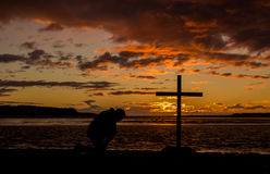 Cross Of Prayer. Man praying at a cross with a colorful sunset in the background Royalty Free Stock Photo