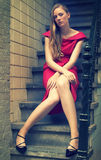 Cross-processed portrait of a pretty fashion model. In red ress sitting on the sair Stock Photos