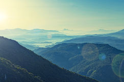 Cross-processed view of sunrise over mountain range Stock Photography