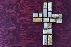 Cross on purple wood out of many little presents Royalty Free Stock Photography