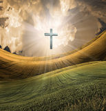 Cross radiates light in sky. Over beautiful landscape Royalty Free Stock Image