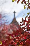 Cross through red autumn leaves. Church or chapel through red autumn fall leaves royalty free stock images