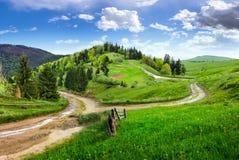 Cross road on hillside meadow in mountain Stock Photos