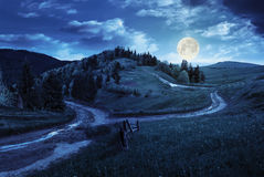 Cross road on hillside meadow in mountain at night Stock Images