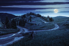Cross road on hillside meadow in mountain at night Stock Photography