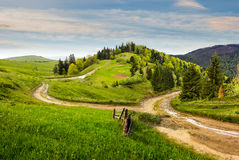 Cross road on hillside meadow in mountain at sunrise Stock Images
