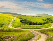 Cross road on hillside meadow in mountain at sunrise Royalty Free Stock Photography