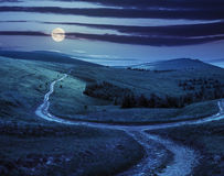 Cross road on hillside meadow in mountain at sunrise at night Stock Photo