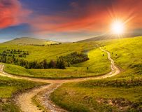 Cross road on hillside meadow in mountain at sunrise at sunset Royalty Free Stock Photo