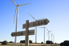 Cross road sign with windmills in the background Green / Clean Stock Photos