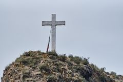 Cross on a rock. Against the background of a light sky royalty free stock photography