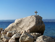 Cross on the rock over the sea. Beautiful beach in Croatia full of rocks and pebbles, with a cross on the rock Royalty Free Stock Images
