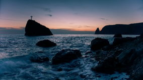 Cross on a rock in the sea stock video
