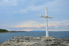 Cross on rocks. A white cross on some rocks near the sea Royalty Free Stock Image