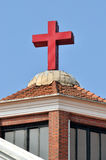 Cross and roof of a Christian church. Roof and red cross of a Christian church architecture under blue sky in Asia, shown as featured element of building and Royalty Free Stock Images