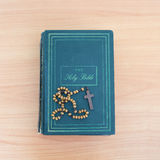 Cross of rosary beads white bible. Royalty Free Stock Image