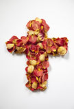 Cross of Rose Petals. A photograph of an arrangement of beautifully colored, dried rose petals in the shape of a cross royalty free stock photo