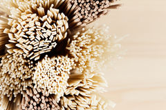 Cross-section of different bundles of raw noodles close up on soft beige wooden board, top view. Cross-section of different bundles  raw noodles close up  soft Royalty Free Stock Image