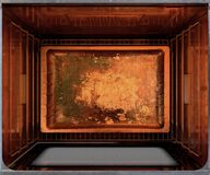 Inside The oven. A cross section top view from above an empty hot operational household oven with an empty tanished baking tray - 3D render Royalty Free Stock Photos