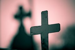 Cross and shadow. Cross with shadow on pink background stock photos