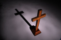 Cross and shadow. Christian wooden Cross in light beam. Shadow on background. Religious concept Stock Photography