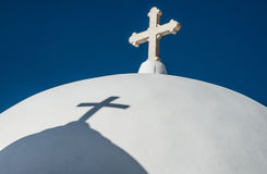 Cross and shadow on dome of a Greek Orthodox church Royalty Free Stock Photography