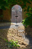 Cross shape gate and cast shadow in a chuch garder Royalty Free Stock Photos