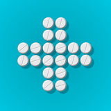 Cross shape with medical pills on blue background Stock Photo