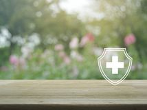Business healthy and medical care insurance concept. Cross shape with shield flat icon on wooden table over blur pink flower and tree in garden, Business healthy royalty free stock images