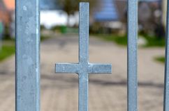 Cross shaped piece of galvanised metal in a rail. Ing or fence outdoors on an urban property in a close up view between parallel bars stock photo