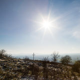 Cross and shining sun. Sunshine over the Christian cross in ravaged country stock image