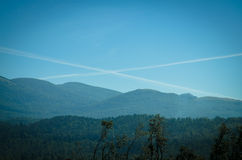 Cross sign in sky. Cross sign from planes in blue sky above mountains Stock Image