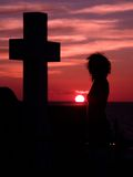 Cross silhouette. Cross and woman silhouette at sunset royalty free stock photography