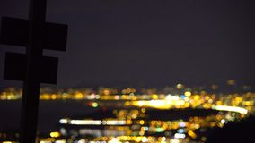 Cross silhouette against luxury life in big illuminated city, aerial night view. Stock footage stock video