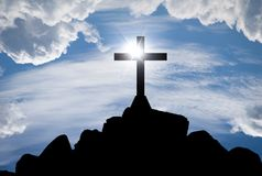 Cross silhouette on the hill. With sunlight and blue cloudy sky Royalty Free Stock Images