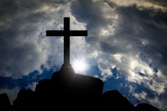 Cross. Silhouette on a mountain with sun light and clouds stock image
