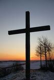 Cross silhouette at sundown in winter Stock Images