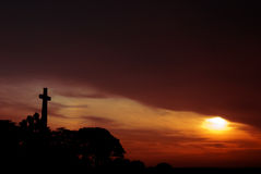 Cross silhouette at sunset. A symbolic cross of the war memorial stands firmly against a backdrop of sunset sky Stock Image