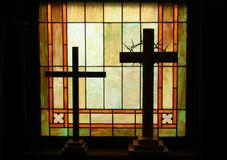 Cross Sill. Silhouette of two religious crosses sitting in stained glass window sill Stock Photos