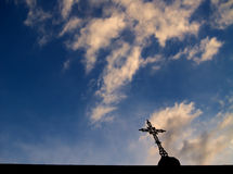 Cross and sky. A metal cross silhouette in a nice blue sky with clouds royalty free stock images