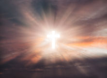 Cross in the sky. Sign of faith. Cross in the sky. Glowing cross with rays of light against of clouds background stock photos