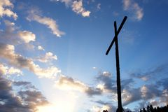 Cross with sky and sun in the background Royalty Free Stock Photos
