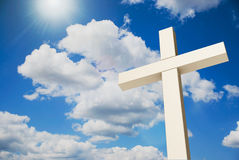 Cross on sky. White wooden cross on the blue sky, three-dimensional rendering, 3D illustration Stock Image