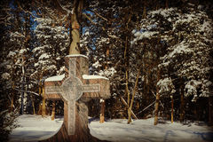 Cross with Snow. A cross in a cemetary with a picture of Jesus on it surrounded by snow covered evergreen trees Royalty Free Stock Images