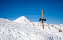 Cross in snowy mountains. The rood against the blue sky and white winter's hills royalty free stock photo